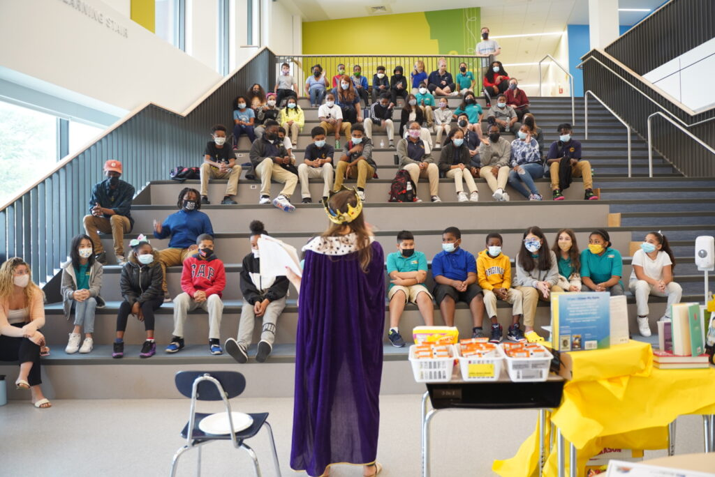 The Reading Queen presents awards and delivers trivia to students seated on the Learning Stair