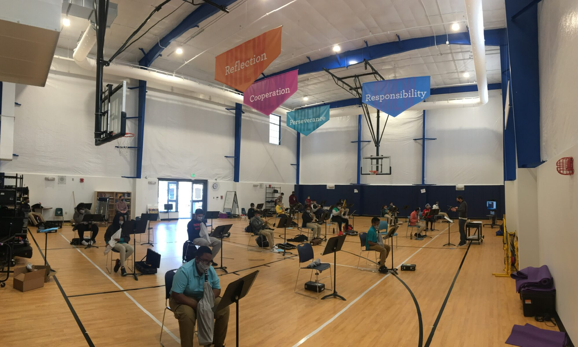Winds and Brass students rehearse in the new Gymnasium with PPE on their instruments and the Crew Qualities above them.